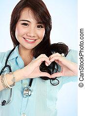 Glückliche junge Krankenschwester mit herzförmigen Händen