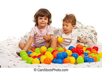 Glückliche Kinder, die mit vielen Bällen spielen