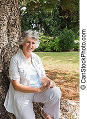 Glückliche reife Frau, die auf dem Baumstamm sitzt