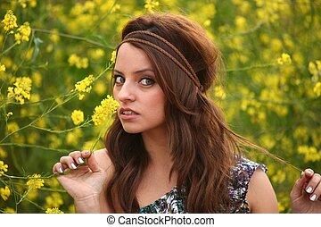 Glückliche, schöne Frau auf einem Blumenfeld