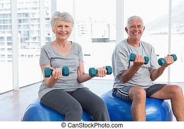 Glückliche Senioren, die mit Dummköpfen auf Fitnessbällen sitzen.