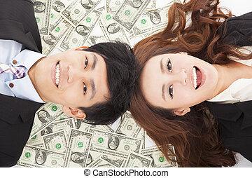Glücklicher Geschäftsmann und Frau liegen auf dem Geld.
