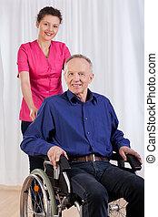 Glücklicher Mann, der im Rollstuhl sitzt.