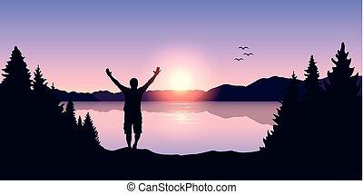 Glücklicher Mann mit erhobenen Armen bei Sonnenaufgang am See.