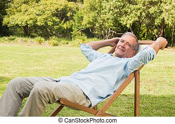 Glücklicher reifer Mann, der auf Sonnenliegen sitzt.