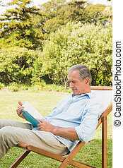 Glücklicher reifer Mann, der Buch liest.