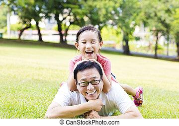 Glücklicher Vater und kleines Mädchen liegen auf dem Rasen.