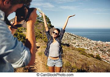 Glückliches junges Paar, das während des Wanderns fotografiert