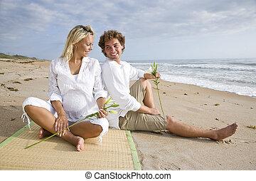 Glückliches junges schwangeres Paar, das sich am Strand entspannt.