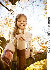 Glückliches kleines Mädchen, das auf einem Baumstamm sitzt.