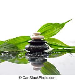 Grün hinterlässt über Zen-Steine-Pyramide auf Wassertropfen