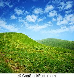 Grüne Hügel und blauer Himmel mit Wolken