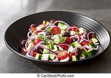 Griechischer Salat in schwarzer Schüssel.