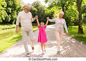 Großeltern und Enkelin im Park.