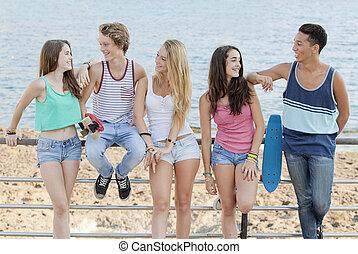 Gruppen von verschiedenen Teenagern am Strand.