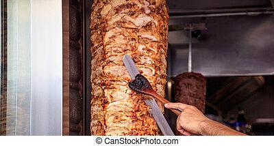 Gyros, Spender. Männerhände mit einem Messer, Schnittscheiben