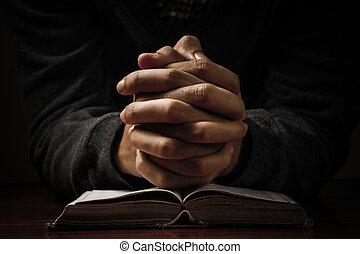 Händchen mit Bibel beten.