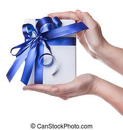 Hände halten ein Geschenk in Paket mit blauem Band, isoliert auf weiß