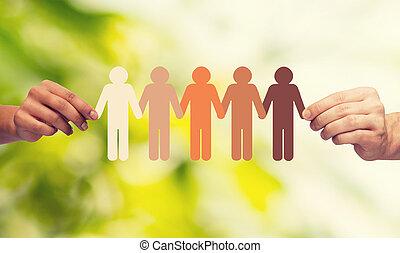 Hände halten Papierkette multirassige Leute.