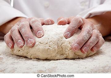 Hände kneten Brotteig.