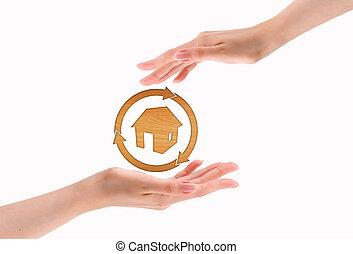 Hände machen Herz mit Holzhaus