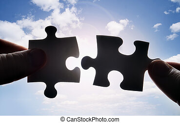 Hände versuchen, zwei Puzzleteile zusammenzufügen