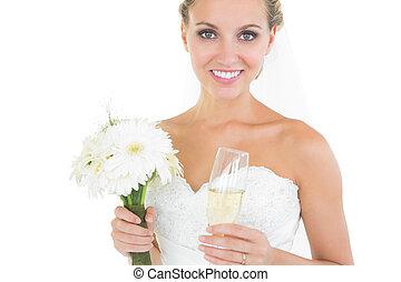 Hübsche Braut mit einem Strauß und einem Champagnerglas