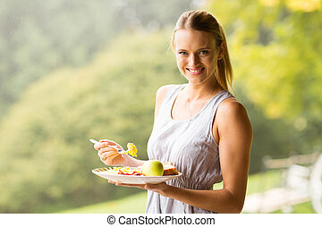 Hübsche Frau, die Frühstück isst.