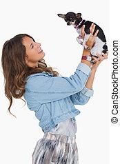 Hübsche Frau hebt ihren Chihuahua