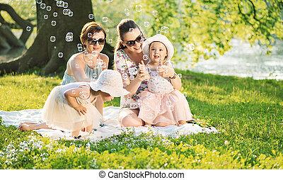 Hübsche Frauen ruhen sich mit kleinen Töchtern auf der Decke aus.