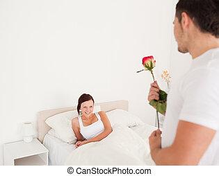 Hübscher Kerl mit einer Rose für seine Freundin