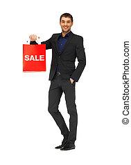 Hübscher Mann im Anzug mit Einkaufstüten