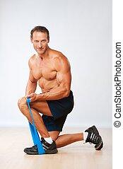Hübscher, muskulöser Mann, der Stretch-Übung macht.
