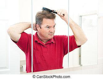 Hübscher reifer Mann, der sich die Haare kämmt
