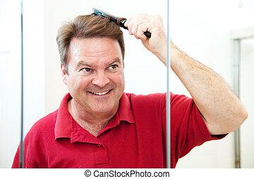 Hübscher reifer Mann kämmt sich die Haare
