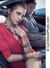 Hübsches elegantes Paar, das ein Luxusauto fährt
