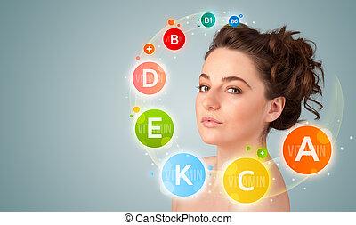 Hübsches junges Mädchen mit farbenfrohen Vitamin-Ikonen und Symbolen