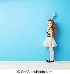 Hübsches Mädchen, das mit Kreide an der Wand schreibt.