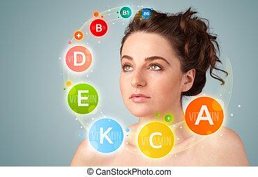 Hübsches Mädchen mit farbenfrohen Vitamin Icons und Symbolen.
