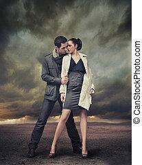 Hübsches Paar, das über stürmische Hintergründe posiert.