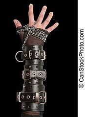 Hand in Lederfesseln auf Schwarz