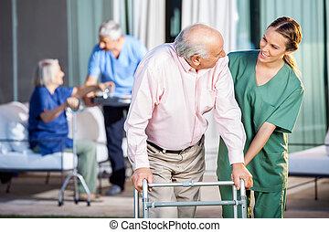 Happy caretaker assisting senior man in using zimmer frame.
