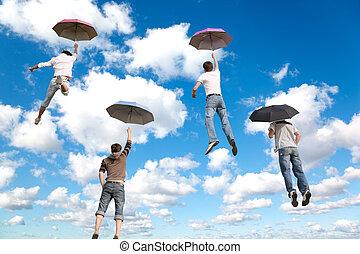 Hinter fliegenden vier Freunden mit Regenschirmen auf White, fluffige Wolken im blauen Himmel kollabieren