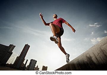 Hispanischer Mann rennt und springt von einer Wand