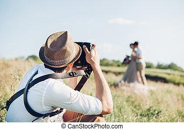Hochzeitsfotograf macht Fotos von Braut und Bräutigam in der Natur, schöne Kunstfoto.