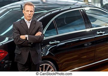Ich liebe Luxusautos. Top-Aussicht von selbstbewussten grauen Haaren Mann in Formkleidung lehnen sich an das Auto und Blick auf die Kamera