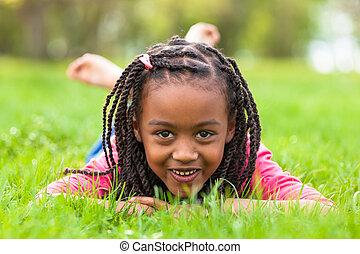 Im Freien Porträt eines süßen schwarzen Mädchens, das auf dem Gras liegt und lächelt - afrikanische Menschen