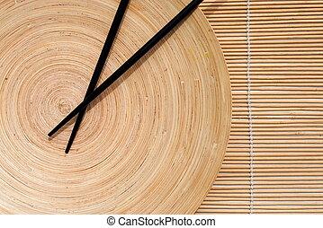Japanische Essstäbchen in hölzerner Schale auf Bambus-Platz-Hintergrund