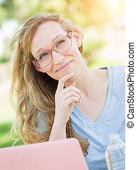Junge erwachsene Frau mit Brille im Freien mit ihrem Laptop.