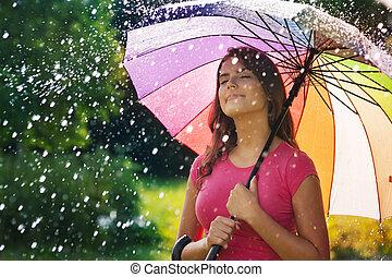 Junge Frau atmet während des Frühlingsregens frische Luft.